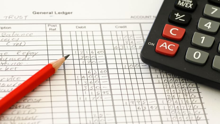 Handwritten Accounting ledger showing bookkeeping using pencil and calculator