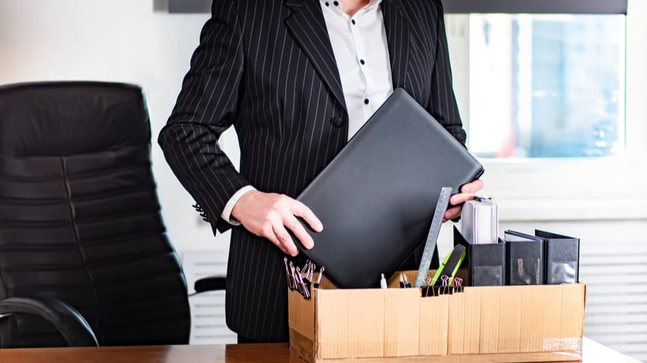 The employee leaves the workplace. A man collects things from the workplace in a cardboard box.