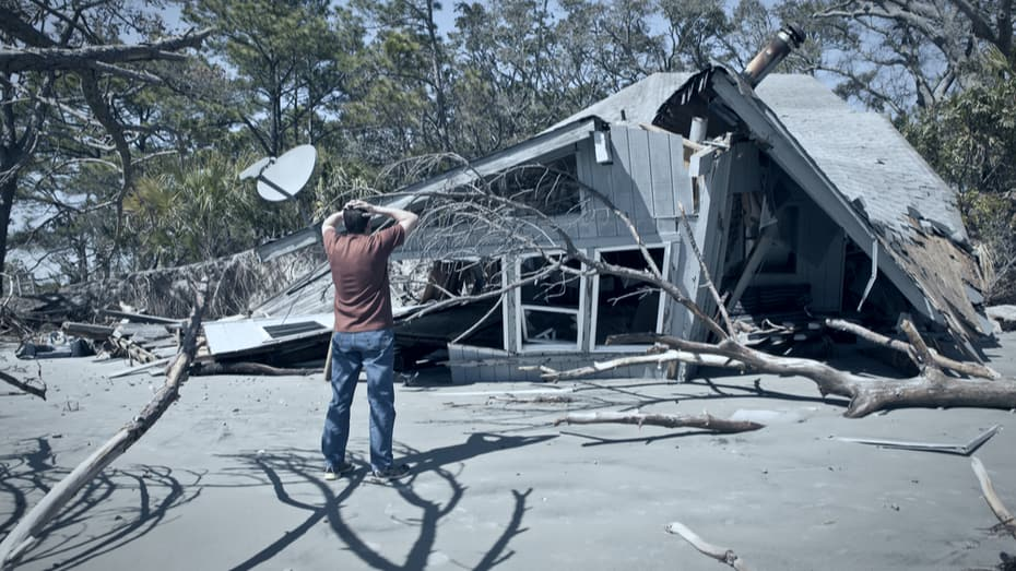 Man looking at his home destroyed after a flood