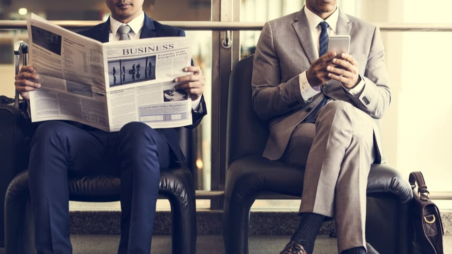 Business men sit to read newspaper